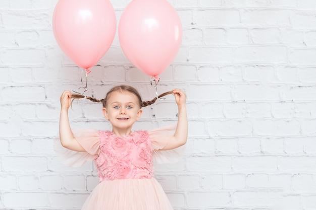 Impreza reklamowa dla dzieci i urodziny uśmiechnięte dziecko z balonami na kucykach