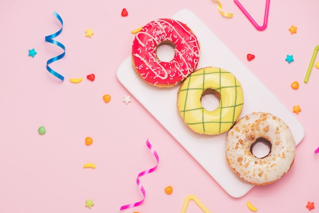 Impreza. różne kolorowe cukierki okrągłe przeszklone pączki i butelki napojów na różowym tle.
