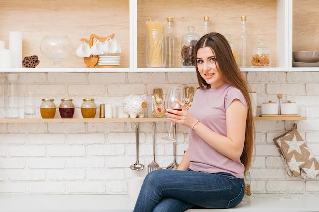 Impreza się skończyła. czas na odpoczynek. piękna młoda kobieta z kieliszek do wina, siedząc na blacie kuchennym.