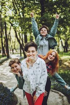 Impreza studencka na świeżym powietrzu. grupa uśmiechnięci rozochoceni dziewczyna przyjaciele świętuje przyjęcia z balonami w parku
