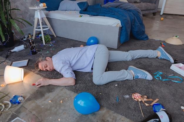 Impreza wykracza poza. widok z góry na pijany dojrzały mężczyzna leżący na podłodze i drzemiący