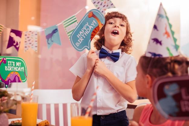 Impreza z dinozaurami. przystojny dzieciak, trzymając uśmiech na twarzy mając urodziny