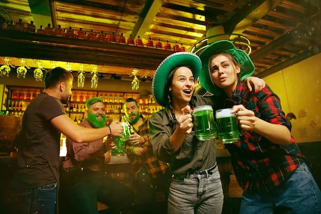 Impreza z okazji dnia świętego patryka. szczęśliwi przyjaciele świętują i piją zielone piwo. młodzi mężczyźni i kobiety w zielonych kapeluszach. wnętrze pubu.