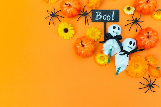 Impreza z okazji halloween zdobione jedzenie dla dzieci dekoracja lizaki w białej serwetce i pająki dynie