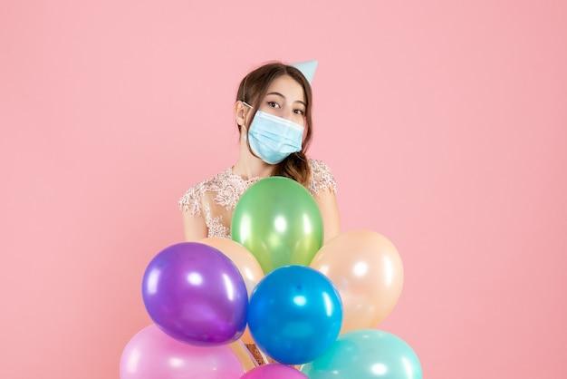 Imprezowa dziewczyna z czapką i maską medyczną, trzymając kolorowe balony na różowo