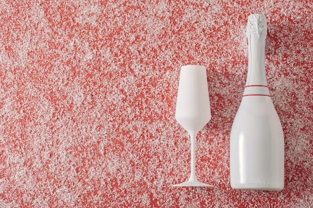 Imprezowe lub świąteczne tło z romantycznym szampanem w czystej białej butelce i flecie na czerwono z rozproszonym zimowym śniegiem i kopią miejsca na życzenia bożonarodzeniowe