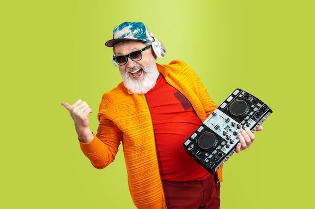 Imprezowicz. portret starszego hipster człowieka w modne okulary na białym tle na tle zielonego studia. koncepcja tech i radosny starszy styl życia. modne kolory, wieczna młodość. miejsce na reklamę.