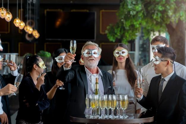 Imprezowicze fantazyjne maski zespołu wykonawczego zbierającego kieliszek do wina do picia i rozmowy, aby świętować.