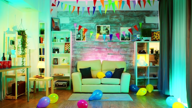 Imprezowo urządzony pokój z neonami na ścianie i kulą dyskotekową, napojami, balonem i frytkami.