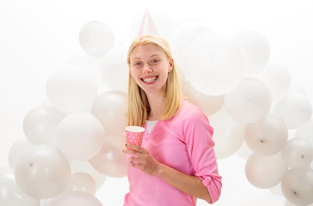 Imprezowy nastrój. piękna dziewczyna w urodzinowym kapeluszu z balonami. obchody wszystkiego najlepszego.