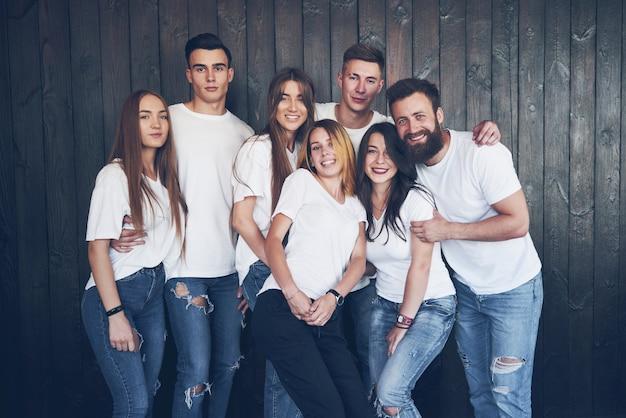 Imprezuj z przyjaciółmi. grupa wesołych młodych ludzi, którzy razem się bawią i coś świętują.