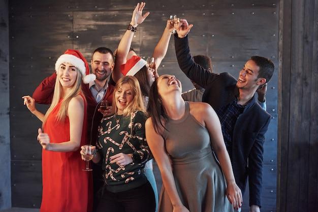 Imprezuj z przyjaciółmi. kochają boże narodzenie. grupa rozochoconych młodych ludzi niosących sparklers i flety szampana tańczących w imprezie nowego roku i wyglądających na szczęśliwych. pojęcia dotyczące wspólnego stylu życia