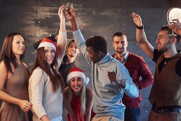 Imprezuj z przyjaciółmi. kochają boże narodzenie. grupa rozochoconych młodych ludzi niosących sparklers i flety szampana, tańczących w imprezie nowego roku i wyglądających na szczęśliwych. pojęcia dotyczące wspólnego stylu życia