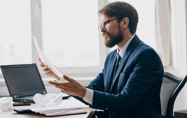 Impulsywny człowiek z białymi kartkami papieru w rękach emocje biuro biznes finanse laptop. wysokiej jakości zdjęcie