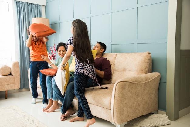 Indian family o zabawnej walce na poduszki na kanapie lub kanapie. rodzice spędzający wolny czas z małymi dziećmi