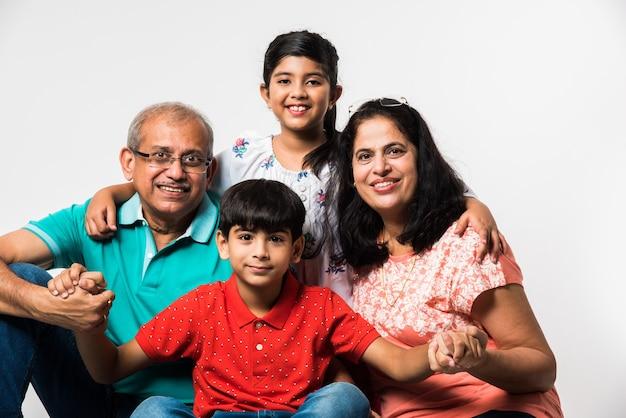Indian kids z dziadkami uśmiechniętymi siedzącymi na białym tle w pomieszczeniu, selektywne skupienie