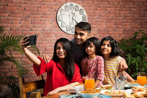 Indian m?odych rodzina czterech jedzenia ?ywno?ci przy stole w domu lub w restauracji. matka z azji południowej, ojciec i dwie córki jedzą wspólny posiłek