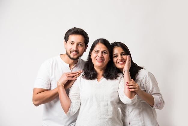 Indian old mother zawstydzające młodych dorosłych dzieci. azjatycka rodzina 3 stojąca na białym tle nad białym tłem. selektywne skupienie