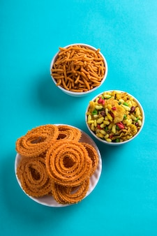 Indian snack: chakli, chakali lub murukku i besan (mąka gram) sev oraz chivada lub chiwada na niebieskim tle. diwali food