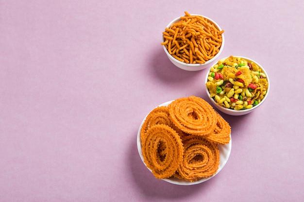 Indian snack: chakli, chakali lub murukku i besan (mąka gram) sev oraz chivada lub chiwada na różowym tle. diwali food
