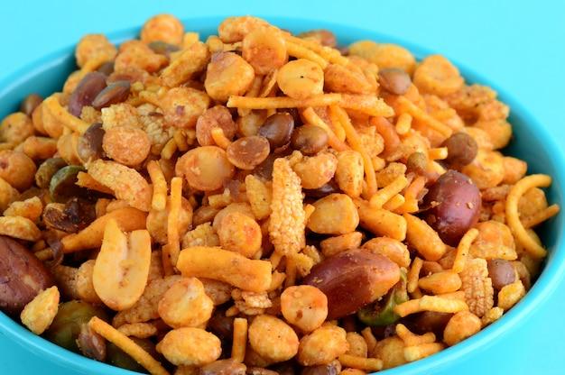 Indian snacks: mieszanka (prażone orzechy z soloną papryką masala, rośliny strączkowe, channa masala dal zielony groszek) w niebieskiej misce w