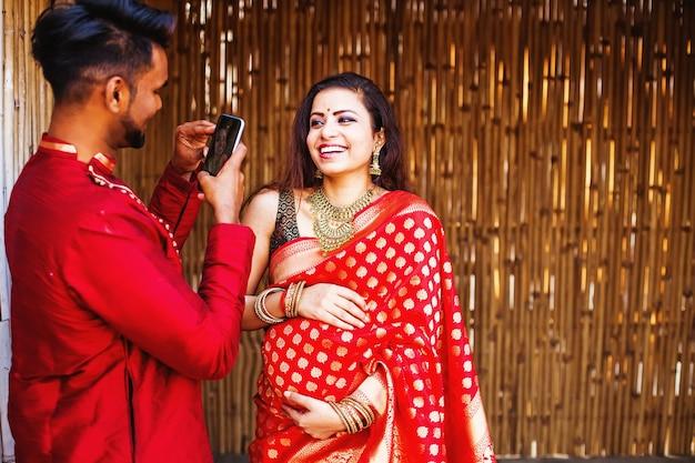 Indianin fotografujący swoją ciężarną żonę ubraną w sari na aparacie w telefonie komórkowym