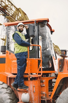 Indianin pracujący. mężczyzna w żółtej kamizelce. mężczyzna w pobliżu ciągnika.