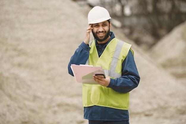 Indianin pracujący. mężczyzna w żółtej kamizelce. mężczyzna z folderem.