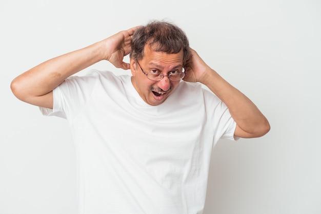 Indianin w średnim wieku na białym tle krzyczy, bardzo podekscytowany, namiętny, zadowolony z czegoś.