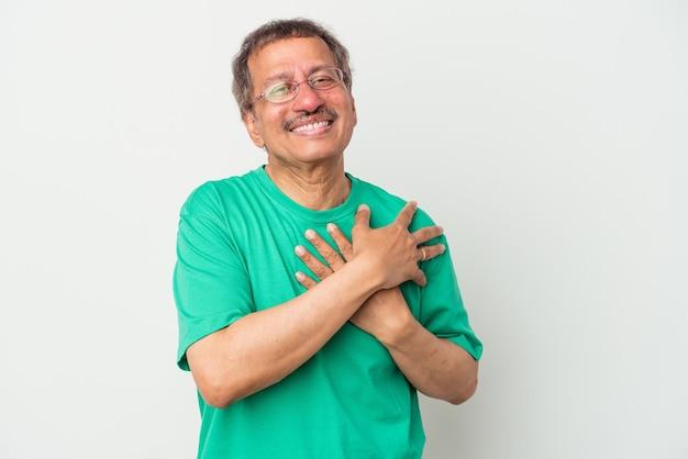 Indianin w średnim wieku na białym tle ma przyjazny wyraz twarzy, przyciskając dłoń do klatki piersiowej. koncepcja miłości.