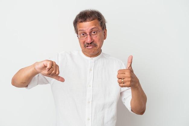 Indianin w średnim wieku na białym tle na białym tle pokazując kciuk w górę i kciuk w dół, trudny wybór koncepcji