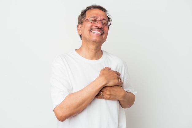 Indianin w średnim wieku na białym tle śmiejąc się trzymając ręce na sercu, pojęcie szczęścia.