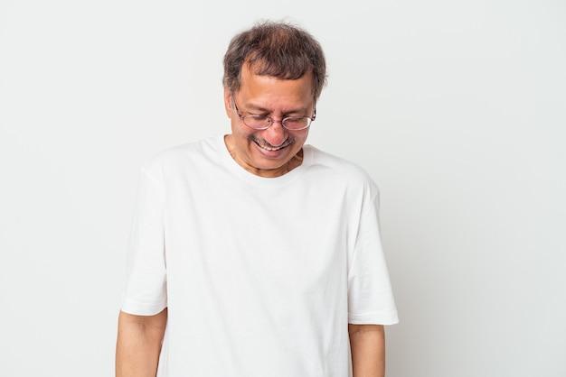 Indianin w średnim wieku na białym tle śmieje się i zamyka oczy, czuje się zrelaksowany i szczęśliwy.
