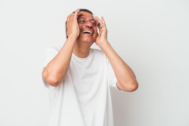Indianin w średnim wieku na białym tle śmieje się radośnie trzymając ręce na głowie. koncepcja szczęścia.