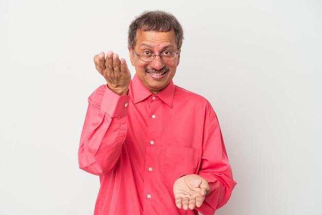Indianin w średnim wieku na białym tle sprawia, że skala z rękami, czuje się szczęśliwa i pewna siebie.