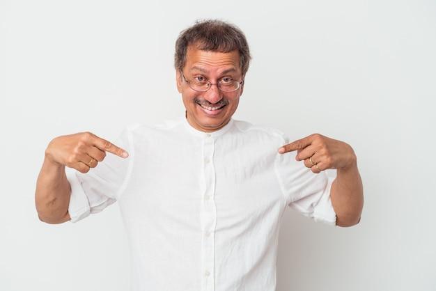 Indianin w średnim wieku na białym tle zaskoczony, wskazując palcem, uśmiechając się szeroko.