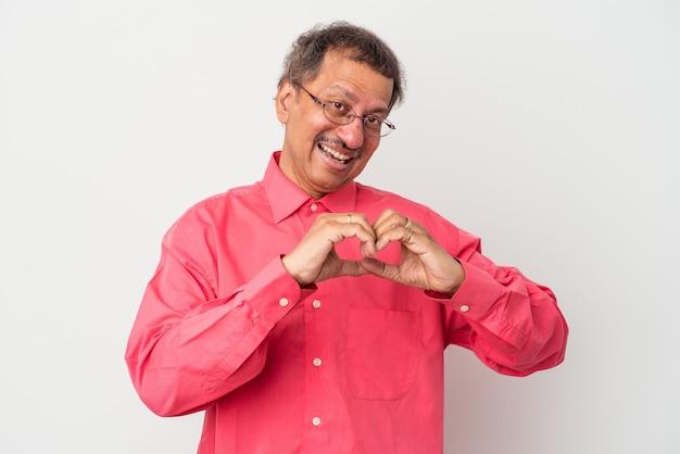 Indianin w średnim wieku uśmiechnięty i pokazujący kształt serca z rękami.