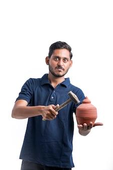 Indianin za pomocą młotka do złamanej gliny skarbonki.