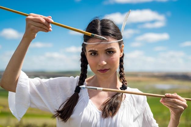 Indianka pozuje w otoczeniu przyrody ze strzałą i łukiem. portret kobiety myśliwego