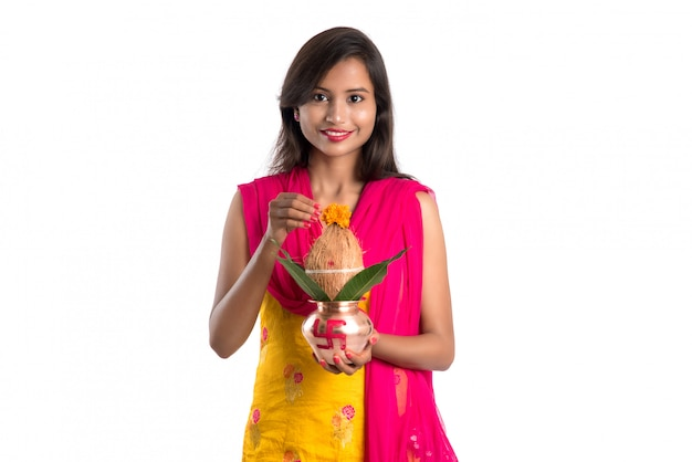 Indianka trzymająca tradycyjną miedzianą kalashę, festiwal indyjski, kalash miedzianą z kokosem i liściem mango z kwiatową dekoracją, niezbędna w hinduskiej pooja.