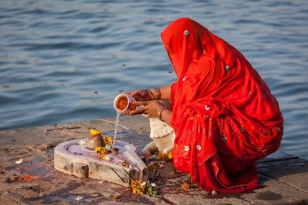 Indianka wykonuje poranną pooja na świętych ghatach z rzeki narmada