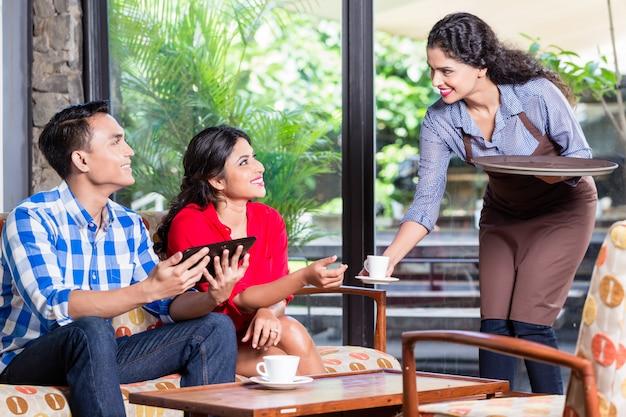 Indiańska kelnerka przyjmuje zamówienia w kawiarni lub restauracji