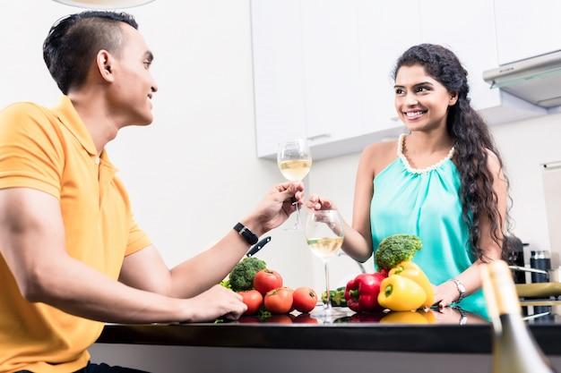 Indiańska kobieta i mężczyzna w kuchni z czerwonym winem
