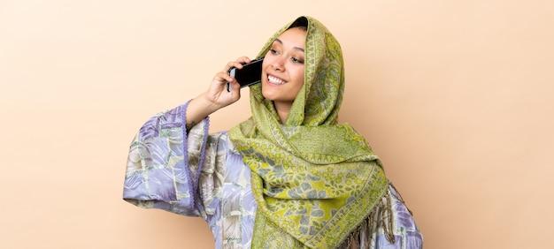 Indiańska kobieta odizolowywająca na beżowym tle utrzymuje rozmowę z telefonem komórkowym