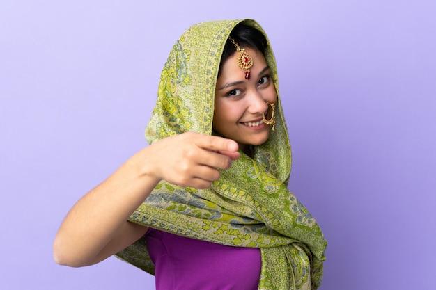 Indiańska kobieta odizolowywająca na purpurach wskazuje przód z szczęśliwym wyrażeniem