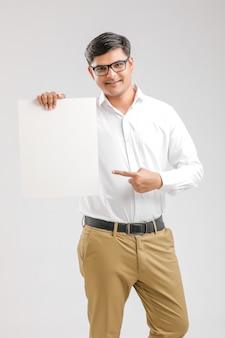 Indiański azjatycki młody człowiek pokazuje pustego signboard