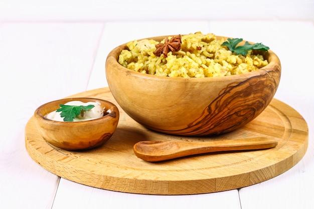 Indiański biryani z kurczakiem, jogurt, pikantność talerz na drewnianym stole. sylwestrowe, świąteczne danie.