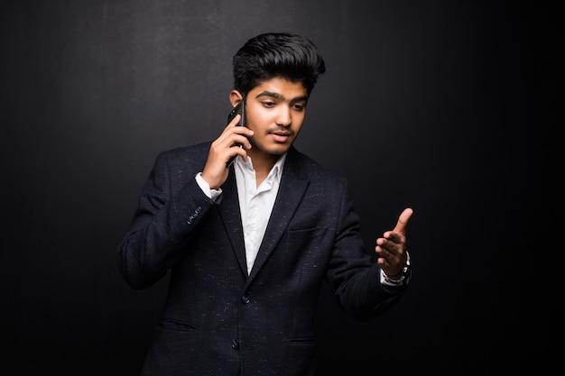 Indiański biznesowy mężczyzna opowiada na telefonie na czerni ścianie