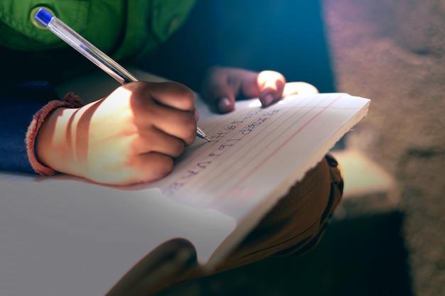 Indiański dziecko pisze na nutowej książce