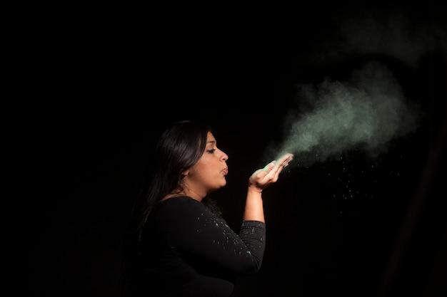 Indiański kobiety dmuchania zieleni pył odizolowywający